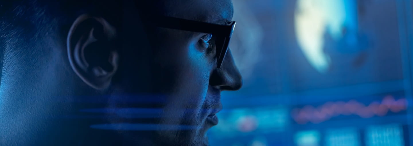 A man with glasses looking at a screen