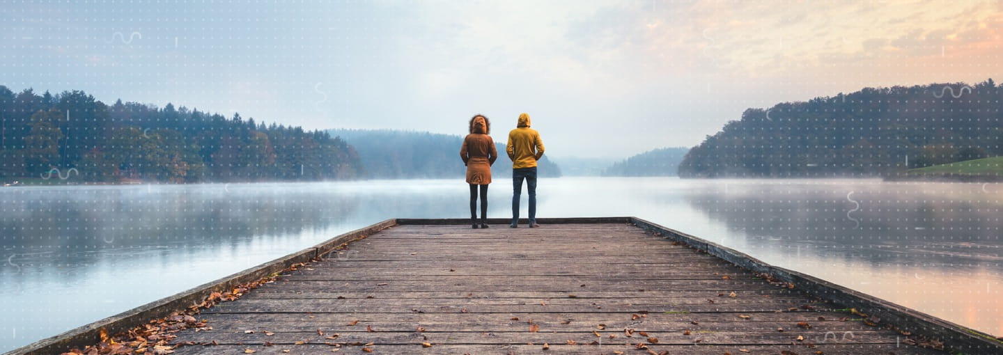 Two people standing at the end of a pier