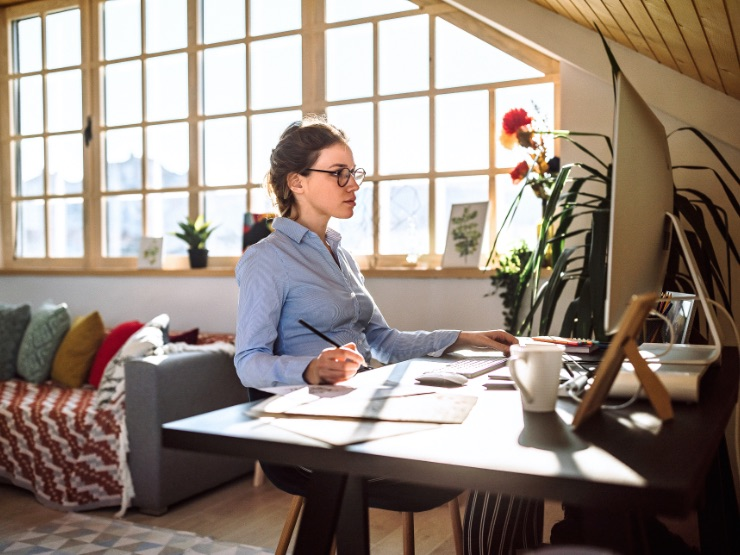 Woman working at desk sunny room