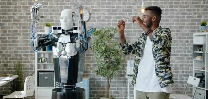 Man standing next to a robot