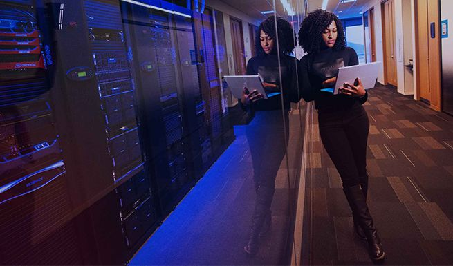 Woman with laptop leaning against a server room window