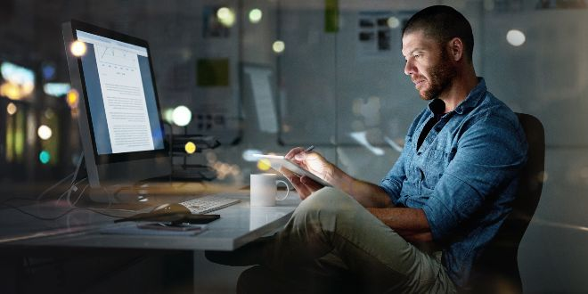 Man sitting in front of a laptop while looking at his mobile phone