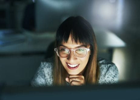 Smiling woman looking at a computer screen
