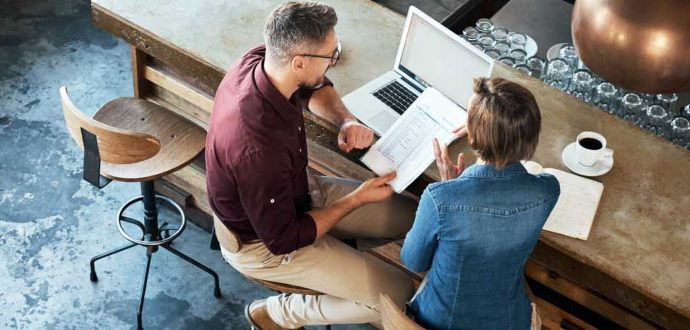 Man and woman sitting at a counter with a laptop and documents